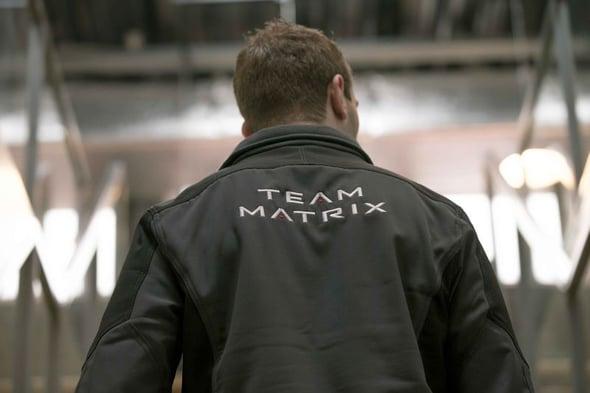 Rugzijde van een man in een vest met een print van het Matrix Fitness-logo