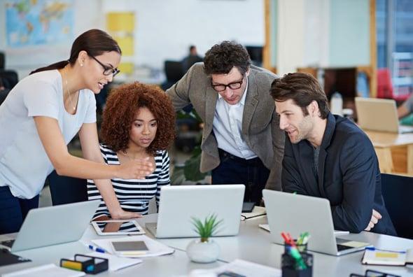 Vier collega's met computers en tablets bespreken samen het nieuwe leerplatform