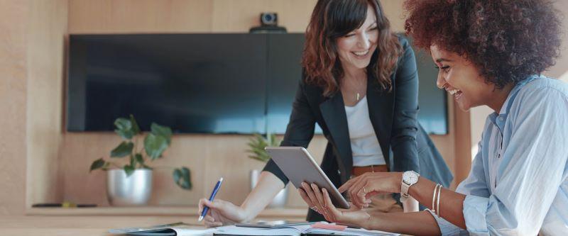 Twee vrouwelijke collega's bekijken samen het leerplatform op een tablet