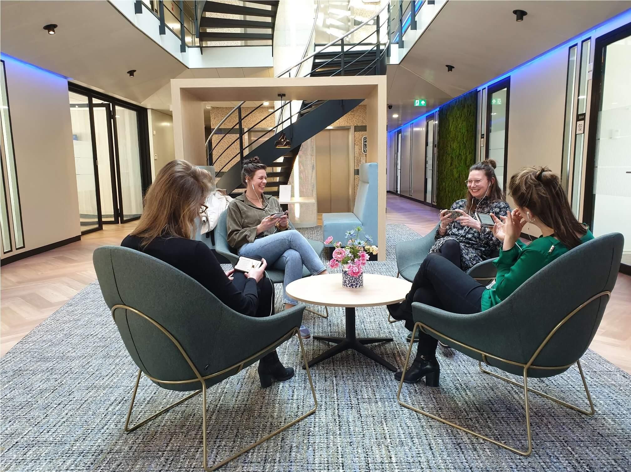 Vier collega's leren op hun mobiele telefoons